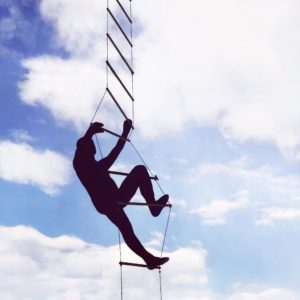 Silhouette of a man climbing a rope ladder into the sky